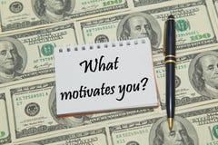 Notitieboekjepagina met tekst WAT U op dollarachtergrond MOTIVEERT Stock Foto's