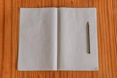 Notitieboekjes en potlood op de houten vloer die van het lijsthardhout worden geïsoleerd Klaar om nota's, rapporten, berichten of stock fotografie