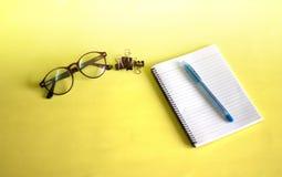 Notitieboekjes, glazen en pennen die op een geel achtergrond het Werk concept worden geplaatst royalty-vrije stock afbeelding