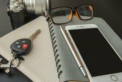 Notitieboekjes, mobiele die telefoons, glazen, camera's, autosleutels op de lijst worden geplaatst stock fotografie