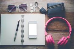 Notizbücher, Becher, Gläser auf einem hölzernen Schreibtisch Lizenzfreies Stockbild