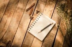 Notizbücher, Bleistifte, Ausrüstung auf dem Bretterboden mit der Morgensonne, die schwach scheint Stockbild