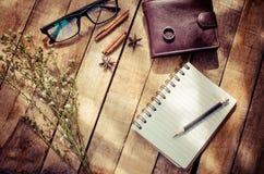 Notizbücher, Bleistifte, Ausrüstung auf dem Bretterboden mit der Morgensonne, die schwach scheint Stockfotografie