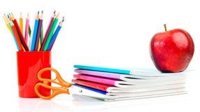 Notizbücher, Bleistifte und Apfel. Lizenzfreie Stockfotos