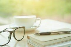 Notizbücher, Brillen, Stifte und Tasse Kaffee auf dem hölzernen tabl Lizenzfreies Stockbild