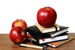 Notizbücher, Stifte und Äpfel auf einem Schreibtisch Stockbilder