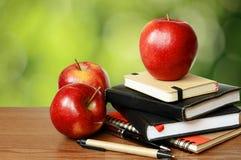 Notizbücher, Stifte und Äpfel auf einer Tabelle Lizenzfreies Stockbild