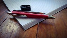 Notizbücher, Stifte und Bleistifte auf hölzernem Stockfoto