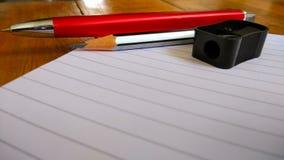 Notizbücher, Stifte und Bleistifte auf hölzernem Stockbild