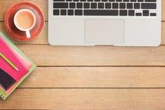 Notizbücher und Laptop auf Schreibtisch- oder Holztabelle Lizenzfreies Stockfoto