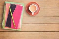 Notizbücher und Tasse Kaffee auf Schreibtisch- oder Holztabelle lizenzfreie stockfotografie
