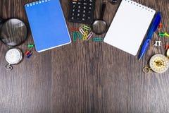 Notizblöcke, Taschenrechner, Vergrößerungsglas, Kompass und Uhr Stockbilder