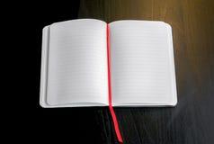 Notizblock auf einer dunklen Tabelle mit rotem Bookmark Lizenzfreies Stockfoto