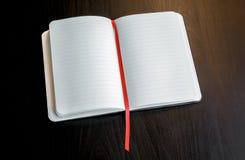 Notizblock auf einer dunklen Tabelle mit rotem Bookmark Lizenzfreie Stockfotografie