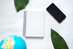 Notizblock auf weißem Hintergrund mit Kugel, grünes Blatt der tropischen Anlage Lizenzfreie Stockfotografie