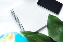 Notizblock auf weißem Hintergrund mit Kugel, grünes Blatt der tropischen Anlage Stockfoto