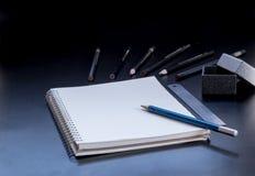 Notizblock, Bleistift, Machthaber und Geschenkbox auf PVC verschalen Schwarzes Stockbild