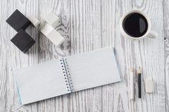 Notizblock, Bleistifte und Kaffee auf Holztisch Lizenzfreies Stockfoto