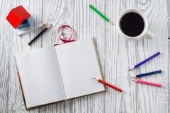 Notizblock, Bleistifte und Kaffee auf Holztisch Lizenzfreie Stockfotos