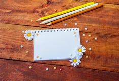 Notizblock, Blumen und Bleistifte Stockfotografie
