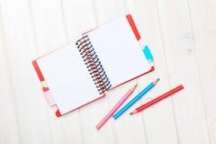 Notizblock des Whtie-Holztisch-freien Raumes und bunte Bleistifte Stockfotografie
