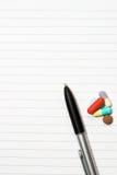 Notizblock, eine Feder, Pillen Lizenzfreies Stockfoto