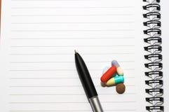 Notizblock, eine Feder, Pillen Stockbilder