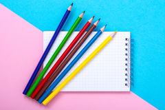 Notizblock für Anmerkungen und bunte Bleistifte auf farbigem Hintergrund Lizenzfreie Stockbilder