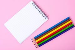 Notizblock für Anmerkungen und bunte Bleistifte auf farbigem Hintergrund Lizenzfreies Stockbild