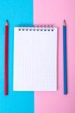 Notizblock für Anmerkungen und bunte Bleistifte auf farbigem Hintergrund Lizenzfreie Stockfotos