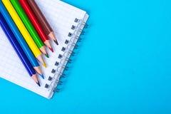 Notizblock für Anmerkungen und bunte Bleistifte auf farbigem Hintergrund Stockbild