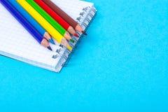 Notizblock für Anmerkungen und bunte Bleistifte auf farbigem Hintergrund Stockfoto