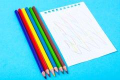 Notizblock für Anmerkungen und bunte Bleistifte auf farbigem Hintergrund Stockfotografie