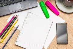 Notizblock, Handy, Papier, Bleistifte und Laptop auf Tabelle Lizenzfreies Stockfoto