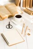 Notizblock, Kaffee und Bücher auf Tabelle Stockfotografie
