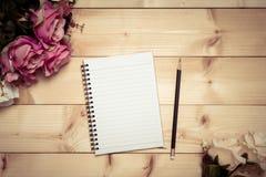 Notizblock mit Bleistift auf dem hölzernen Hintergrund Stockbilder