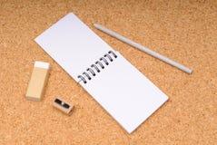 Notizblock mit Bleistift, Radiergummi und Bleistiftspitzer Stockbilder