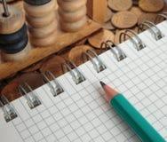 Notizblock mit Bleistift und Abakus Stockbild