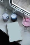 Notizblock mit Blinddeckel für Text auf Fensterbrett Brennen Sie heraus die Kerzen mit Rauche, Smoothiegetränk im hohen Glasbeche Stockbilder