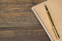 Notizblock mit Goldbrunnen-Pen On The Old Wood-Tabelle Stockbilder