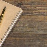 Notizblock mit Goldbrunnen-Pen On The Old Wood-Tabelle Lizenzfreie Stockbilder