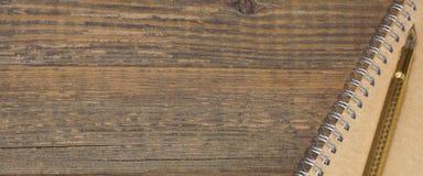 Notizblock mit Goldbrunnen-Pen On The Old Wood-Tabelle Stockfotos