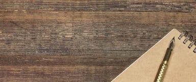 Notizblock mit Goldbrunnen-Pen On The Old Wood-Tabelle Lizenzfreies Stockbild