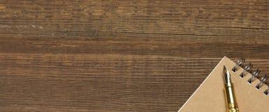 Notizblock mit Goldbrunnen-Pen On The Old Wood-Tabelle Lizenzfreies Stockfoto