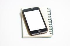 Notizblock mit intelligentem Telefon auf weißem Hintergrund Stockfoto