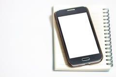 Notizblock mit intelligentem Telefon auf weißem Hintergrund Stockbilder