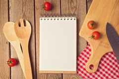 Notizblock mit Leerstelle mit Kochgerät auf Holztisch Lizenzfreies Stockbild