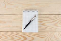 Notizblock mit Stift auf Holztisch Stockfotos