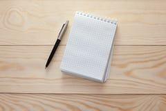Notizblock mit Stift auf Holztisch Stockfoto