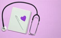 Notizblock mit Stift, dekoratives Herz, Stethoskop auf rosa Pastellb lizenzfreies stockbild